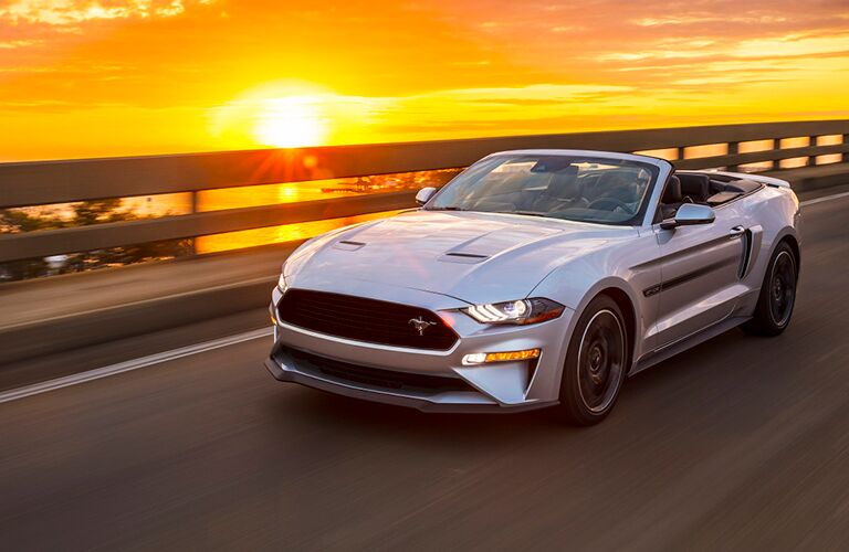 Silver 2019 Ford Mustang driving on waterfront highway at sunset