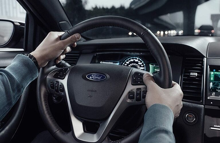 Hands gripping steering wheel of 2019 Ford Taurus