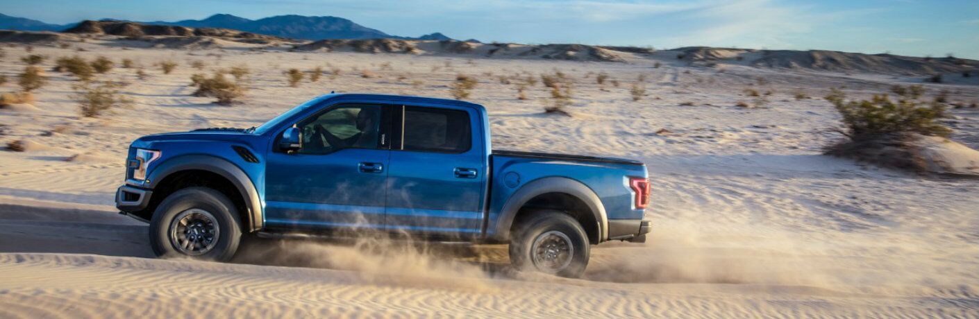 Profile view of blue 2019 Ford F-150 Raptor driving in sand
