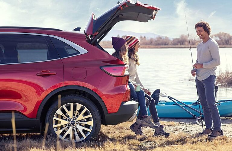 A grinning fisherman approaches two women who are sitting on the cargo area of a 2020 Ford Escape.