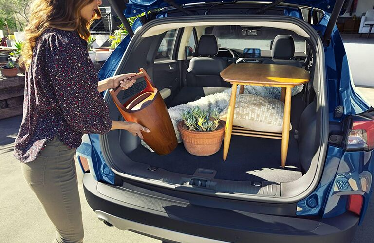 A woman placing items in the rear cargo area of a blue 2020 Ford Escape.