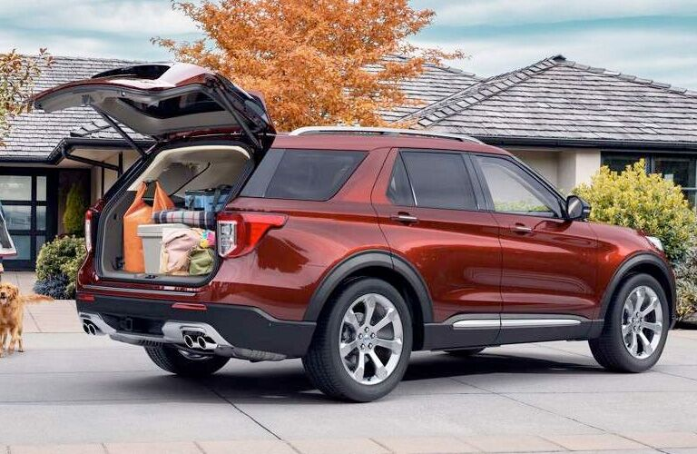 2020 Ford Explorer exterior back fascia trunk open showing cargo space and passenger side in front of house and tree