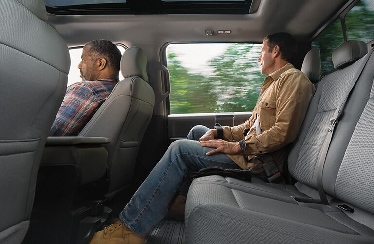 Two rugged men seated front and back inside a 2020 Ford F-150 truck.