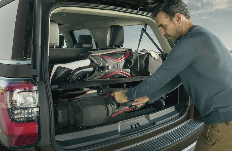 2020 Ford Expedition with hatch open and man loading up golf clubs