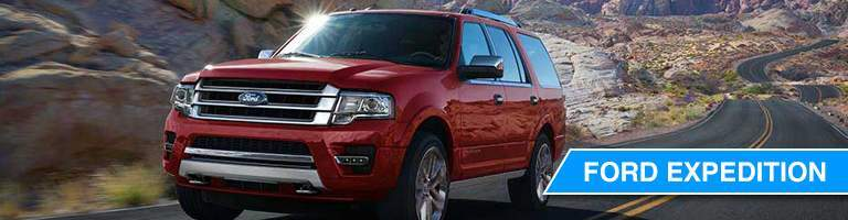 Red Ford Expedition driving down desert road with landscape surrounding
