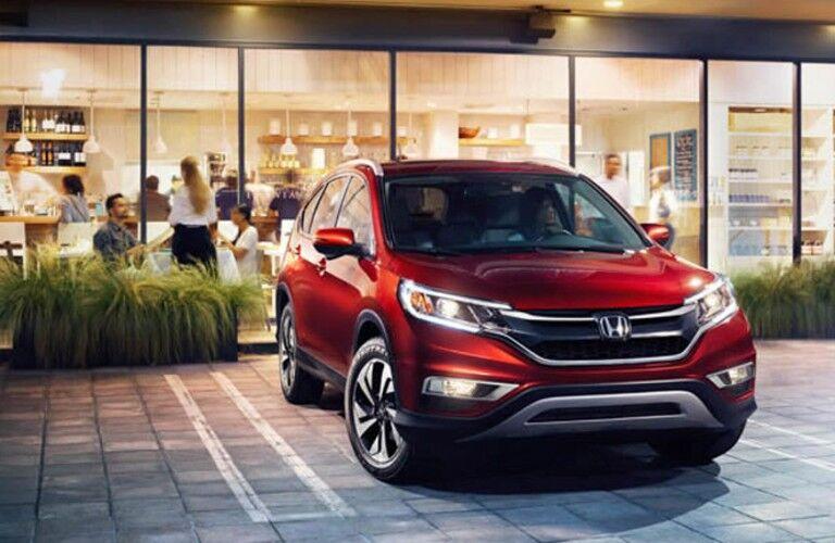 2014 Honda CR-V red exterior front fascia passenger side parked outside of restaurant