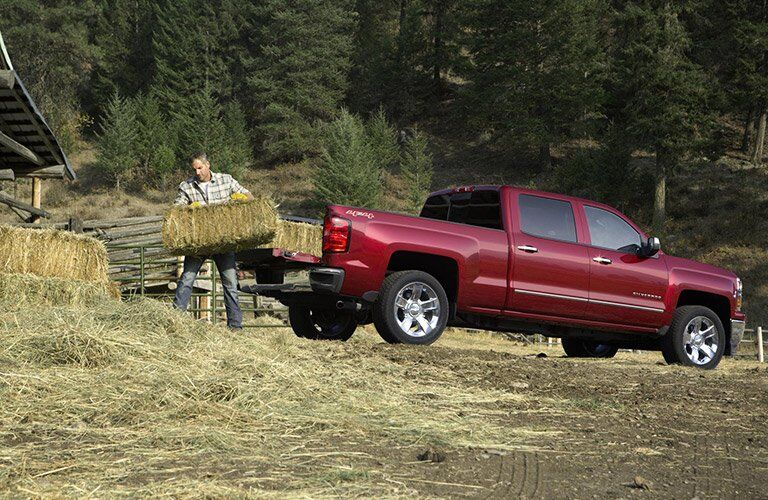side view of the 2016 Chevy Silverado being loaded with hay or straw