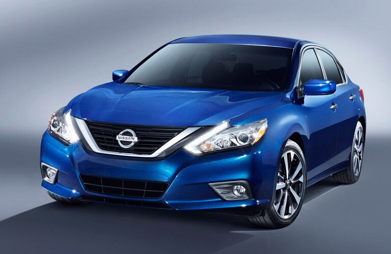 blue 2016 Nissan Altima seen from the front with a grey background