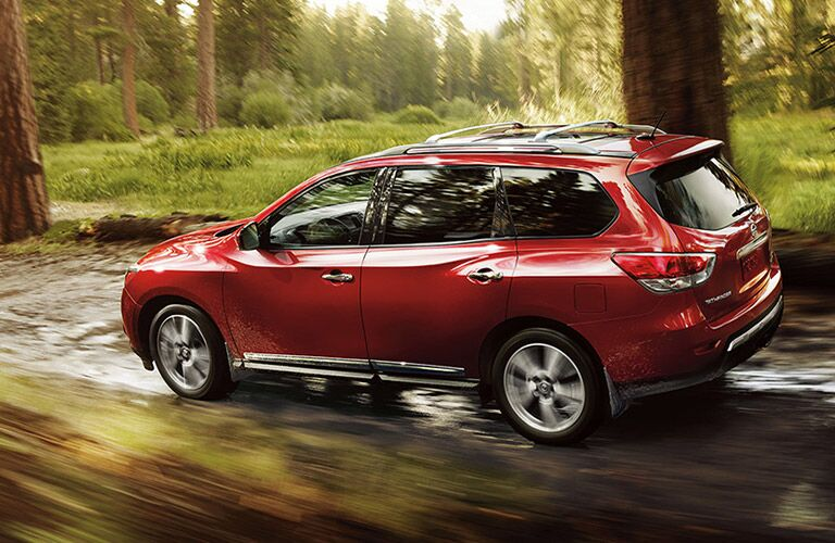 side view of a red 2016 Nissan Pathfinder driving through the forest