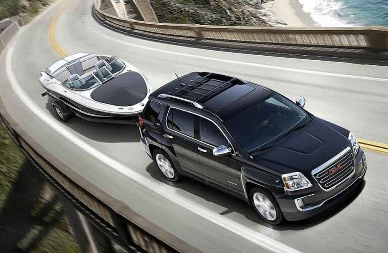 GMC Terrain drives down a highway towing a boat effortlessly.