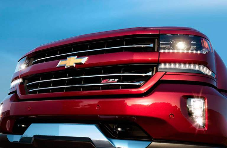 close up view of the grille of a red 2017 Chevy Silverado