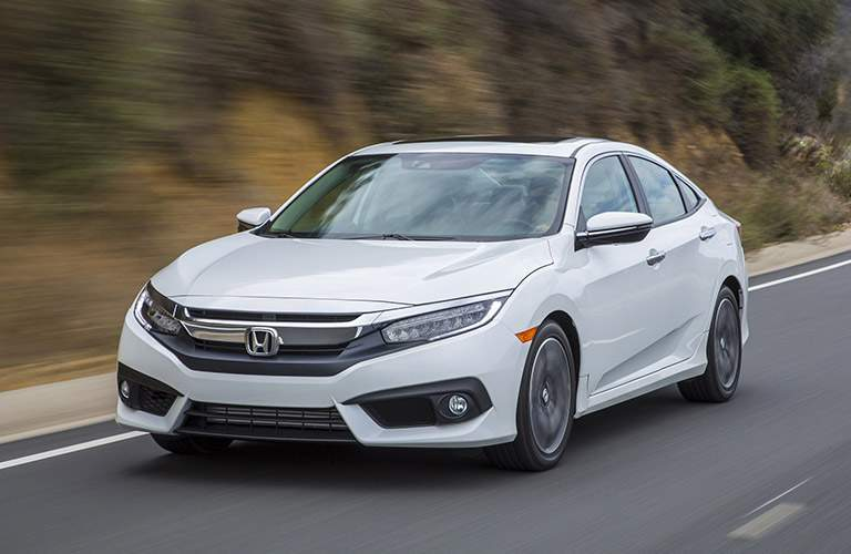 White 2017 Honda Civic Sedan drives down a highway.