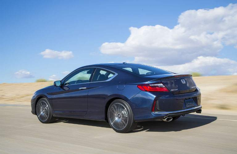 2017 Honda Accord coupe seen from the side in dark blue against a pale blue sky