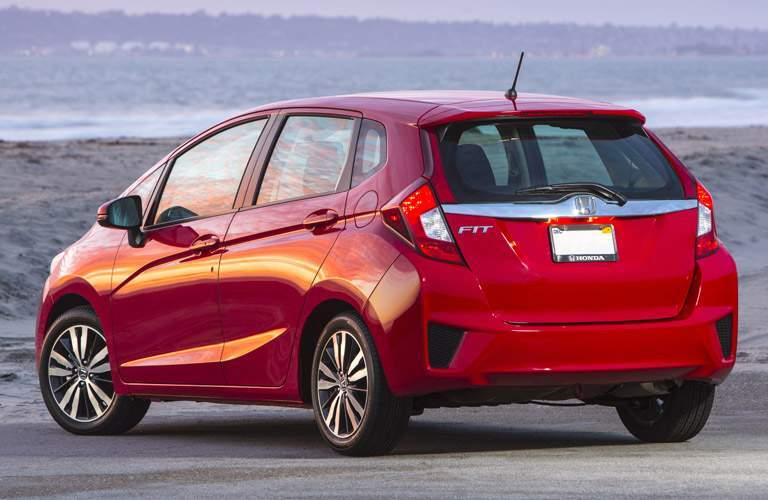 rear view of a red 2017 Honda Fit hatchback parked in front of the ocean