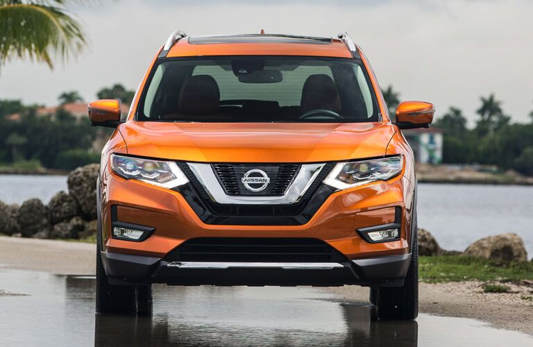 Orange 2017 Nissan Rogue parked on a rainy day. Head on exterior view.