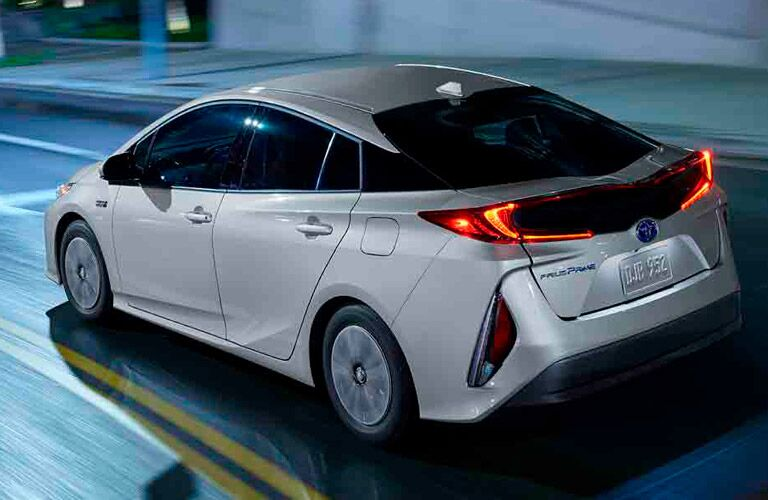 White 2017 Toyota Prius Prime drives down a city street at night.