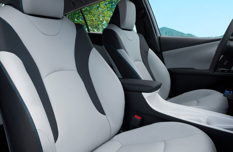 Interior front row of futuristic white and black seats in a 2017 Toyota Prius.