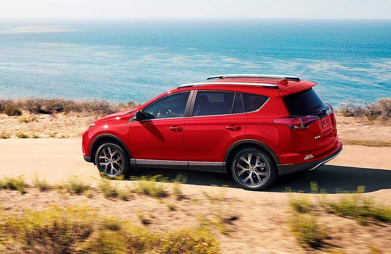Red 2017 Toyota RAV4 cruises along a seaside path.