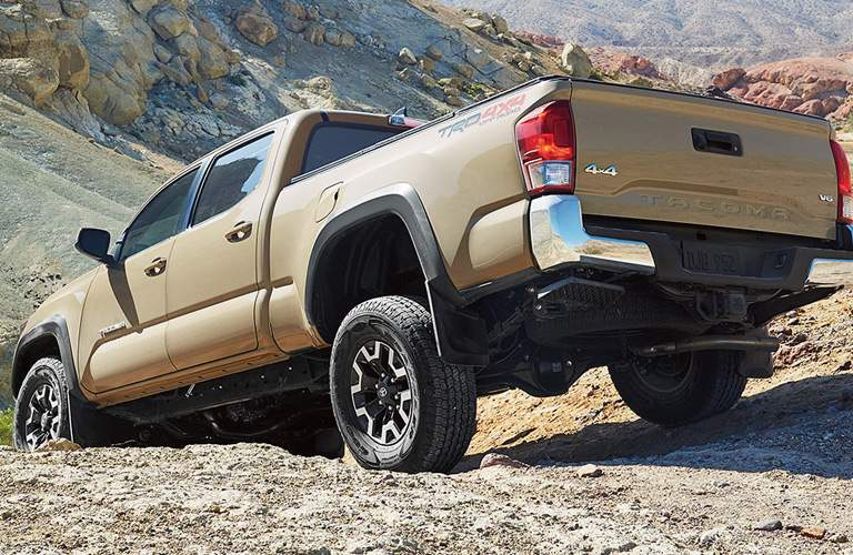 rear view of a brown 2017 Toyota Tacoma in the rocks