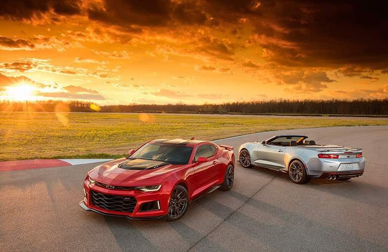 coupe and convertible versions of the 2017 Chevy Camaro against a gorgeous sunset