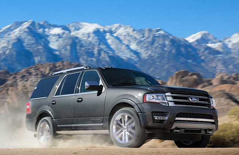 2017 Ford Expedition driving in dust with a background of mountains