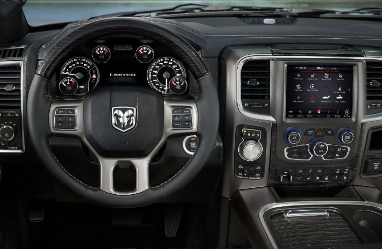 Steering wheel, dash, and infotainment console view within the interior of a 2018 RAM 1500.