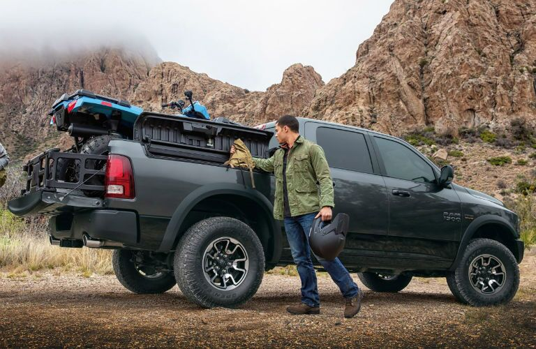 A man polishes the side of his 2018 RAM 1500, which is parked by a rocky hill in the wilderness.