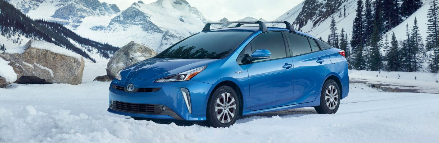 Blue 2019 Toyota Prius parked out amidst snowy mountains and pines.