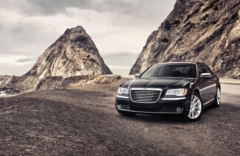 Black 2011 Chrysler 300 in front of cliff and water from exterior front driver side