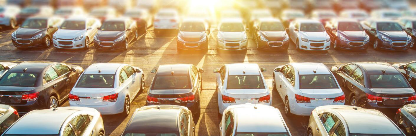 A multitude of cars are parked on a lot and seen from a raised angle. Bright sunlight blasts over them from the distance.