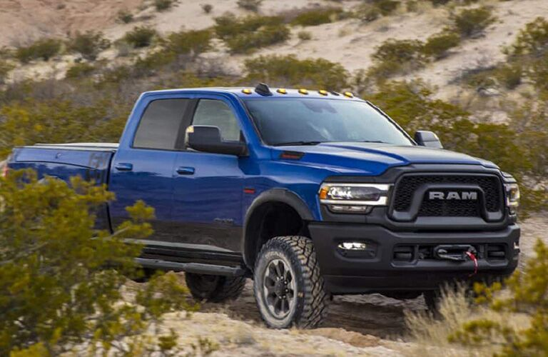 A front-right quarter photo of a heavy-duty Ram pickup truck in the desert.