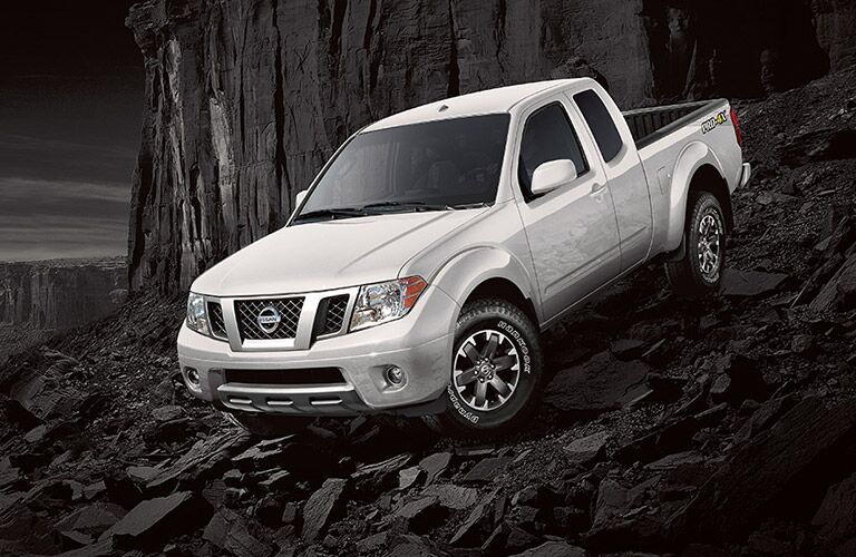 A photo of the Nissan Frontier parked on some rocks.
