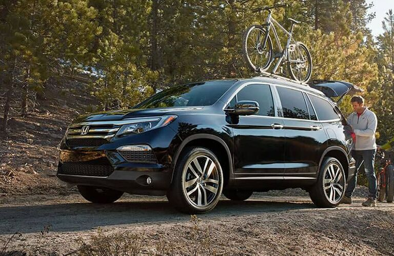 A used Honda Pilot with a roof-top bike rack in the woods.