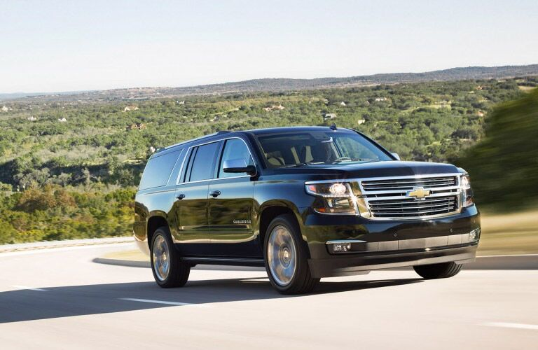 A photo of a Chevy Suburban on the road.