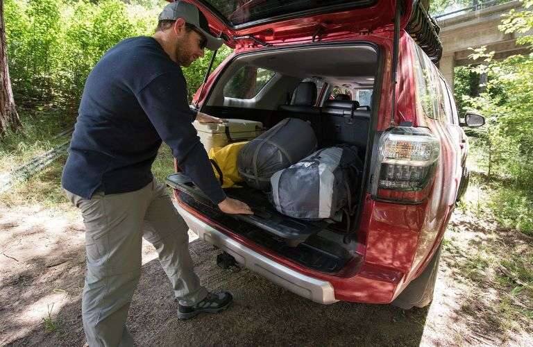 The cargo area of a used Toyota 4Runner filled with camping gear.
