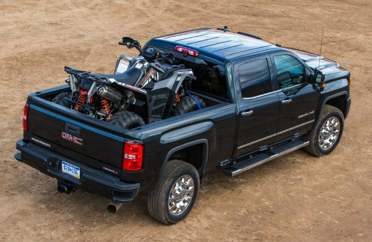A photo of a used GMC Sierra 2500HD Denali with a four-wheeler in the cargo bed.