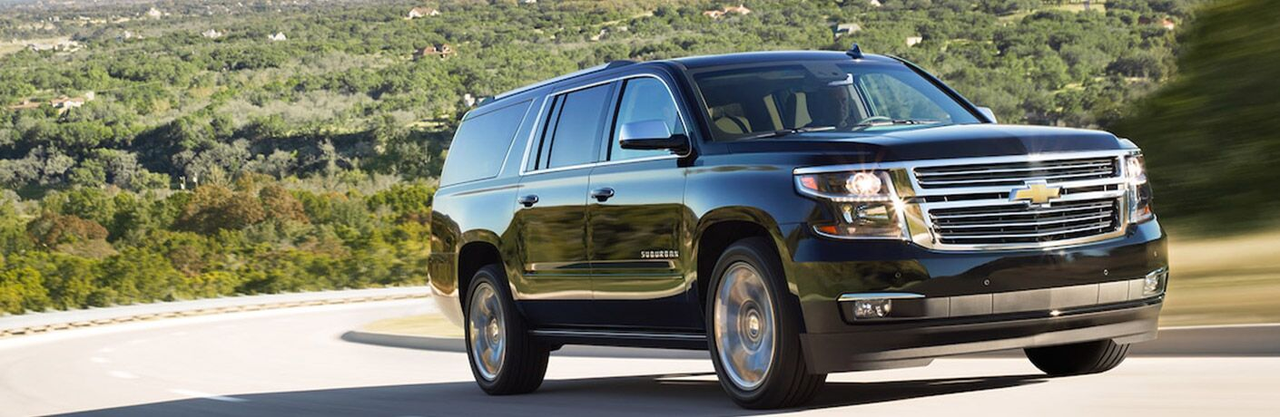A front right quarter photo of a pre-owned Chevy Suburban on the road.