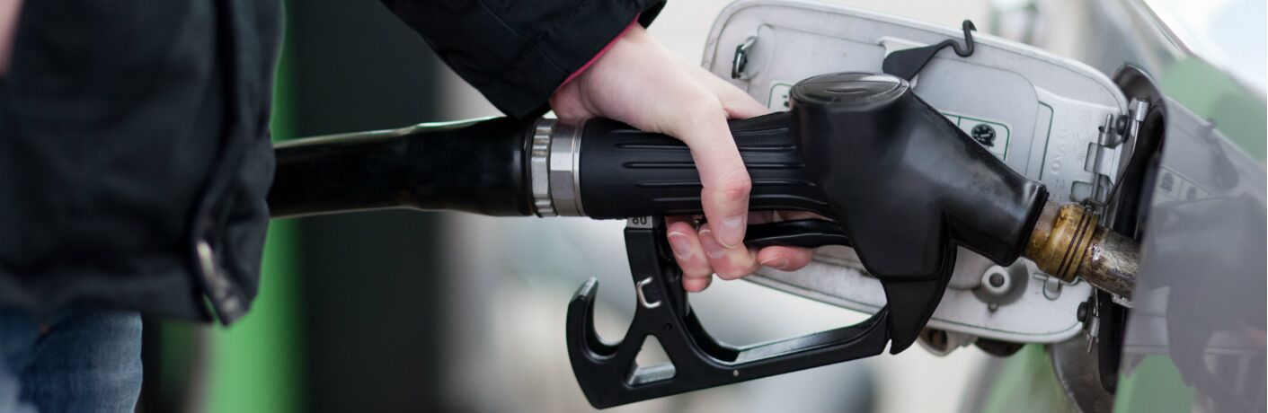 A hand fills up a gas tank on a car.