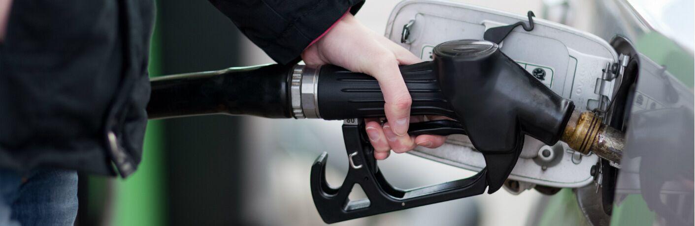 A hand fills up a gas tank on a car.