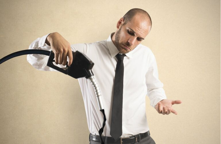 A man wearing a shirt and tie in a building holds a gas filling mechanism, from the end of which comes a strange black fluid. He shrugs.