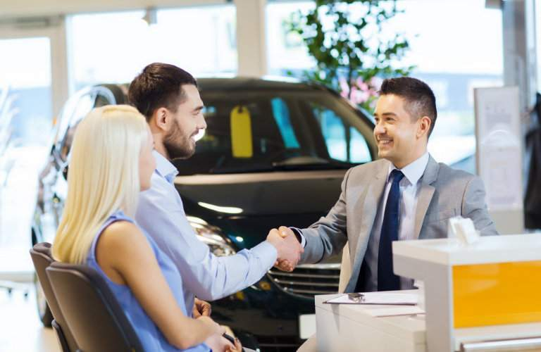 car dealership employee shaking hands with seated customers with a car in the background