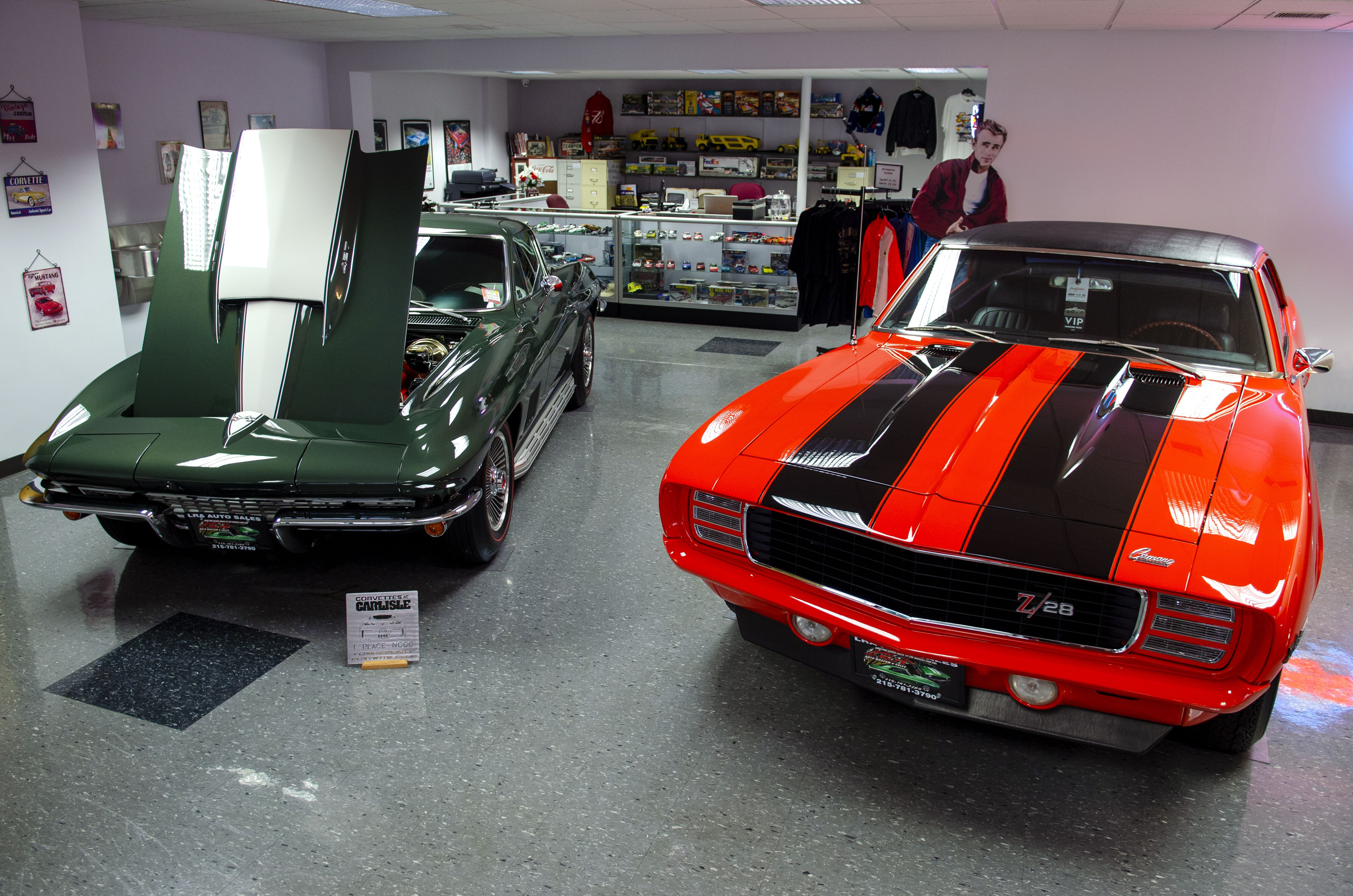 classic vehicle with hood up in showroom