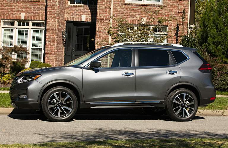 profile of a grey 2018 Nissan Rogue in front of a house