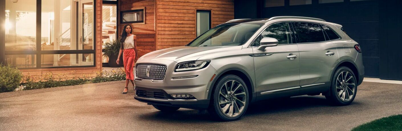 2021 Lincoln Nautilus parked outside of a house and a woman walking up to it