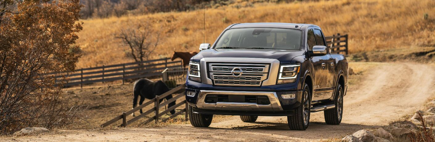 2021 Nissan TITAN going past a pasture of horses