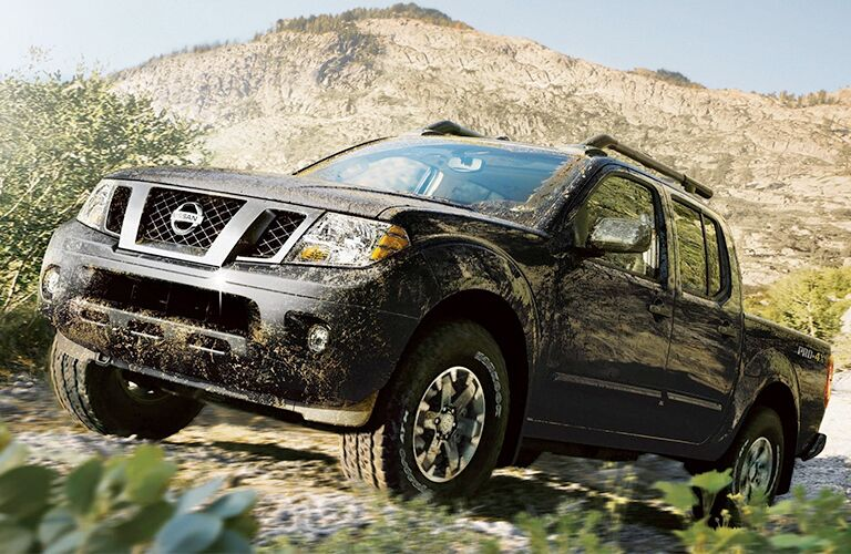 2019 Nissan Frontier black driving uphill muddy