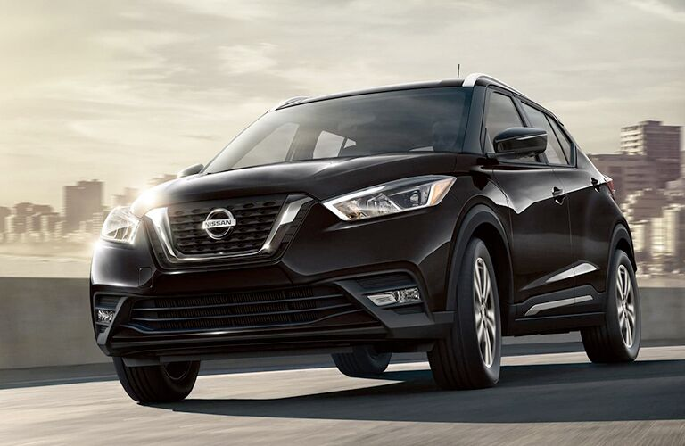 2019 Nissan Kicks black driving across bridge with city skyline in background