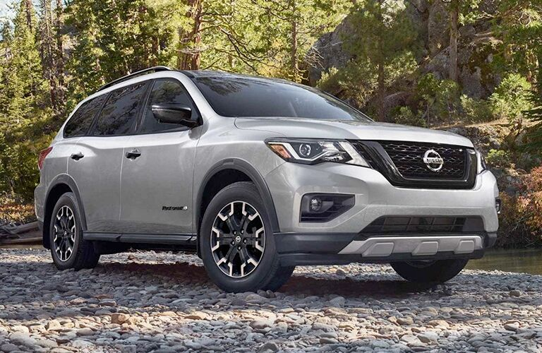 2019 Nissan Pathfinder silver parked on rocks in forest