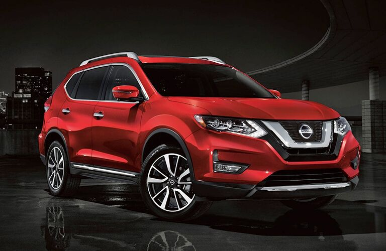2019 Nissan Rogue red parked on reflective black surface at night