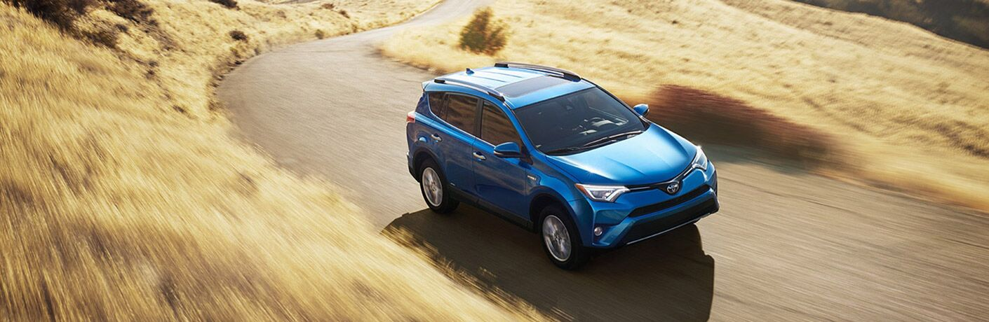 blue 2018 toyota rav4 hybrid driving on farm road